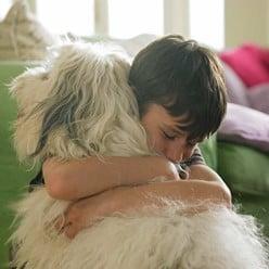 A kid giving his dog a hug